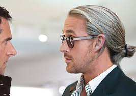 The ever popular Ryan Gosling man bun sits low on the back of his head.